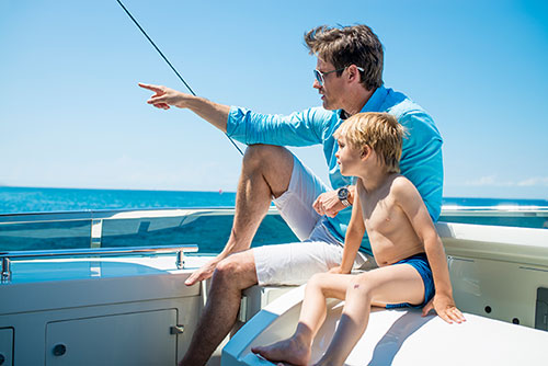 Father and son on motor yacht deck