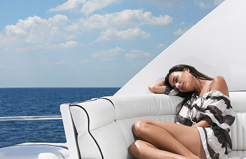 Woman lying on a sofa on the deck of a boat